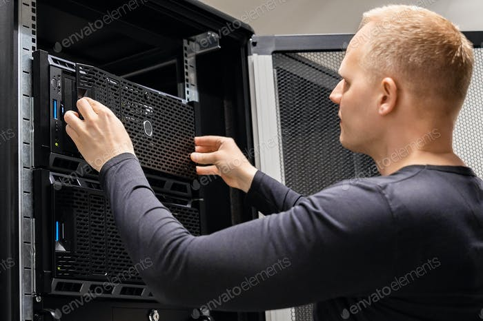 Male Technician Installing Servers In Enterprise Datacenter for Cloud Hosting