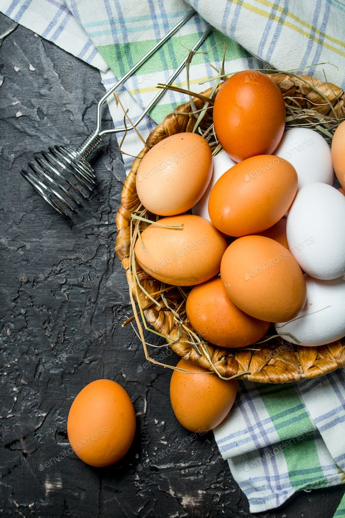 Eggs in a basket with a whisk and napkin.
