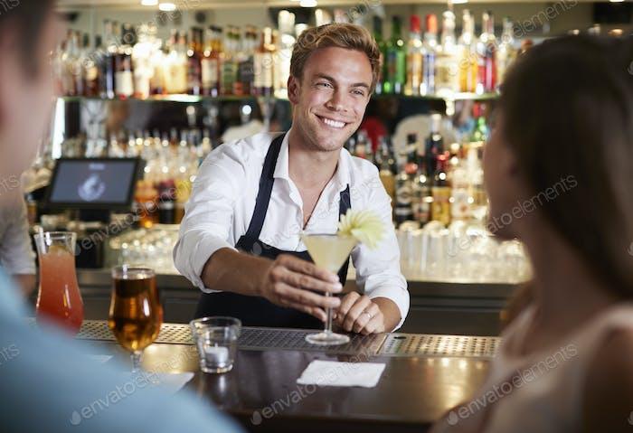 Barman servieren Cocktail zu weiblichen Kunden in Bar