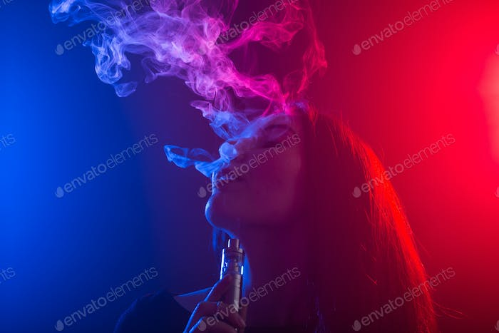 Close up portrait of vaping girl in neon blue and red light.