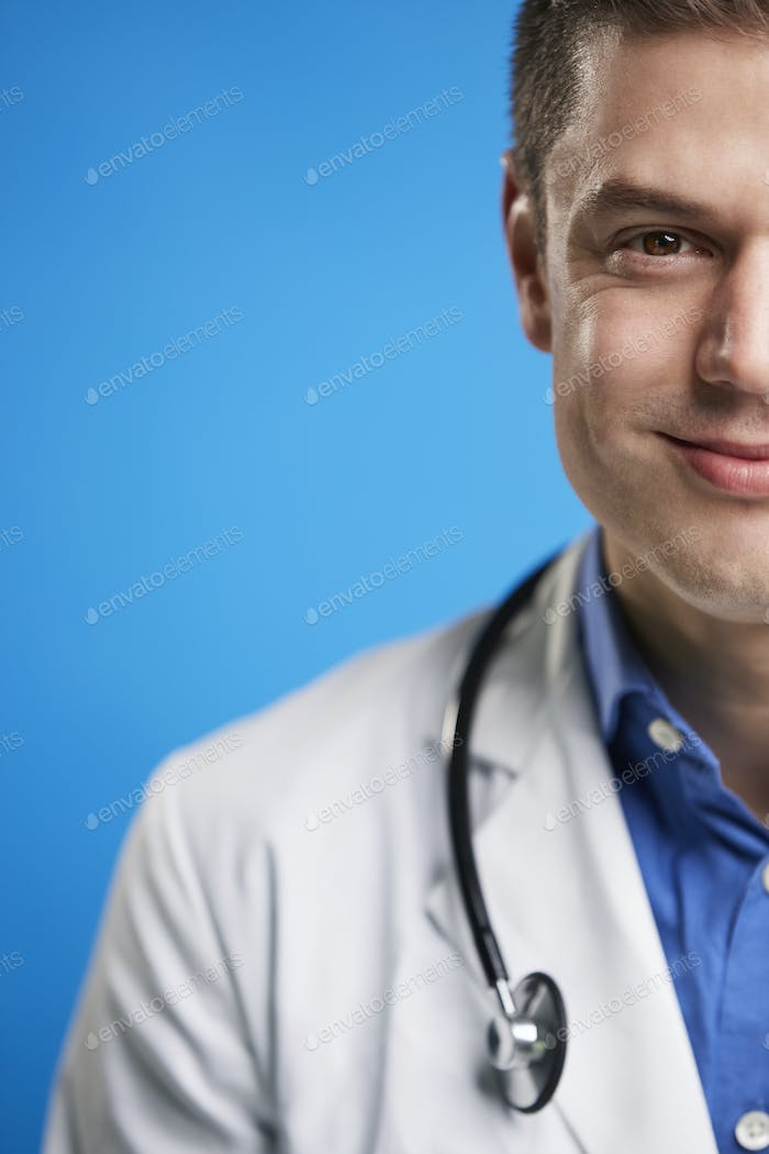 Smiling white male doctor with stethoscope, vertical, crop