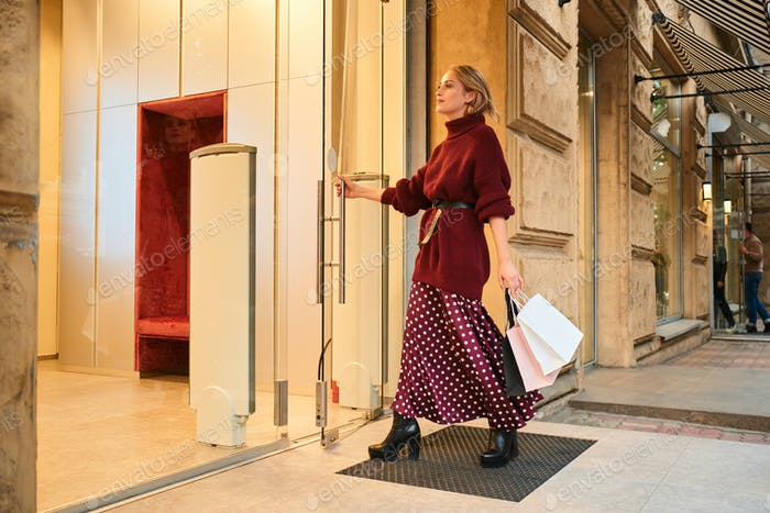Attractive stylish blond girl with shopping bags happily opening store door