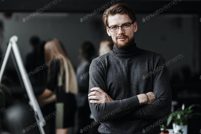 Der Kerl gekleidet in lässigen Bürostil Kleidung und Brille steht im modernen Büro