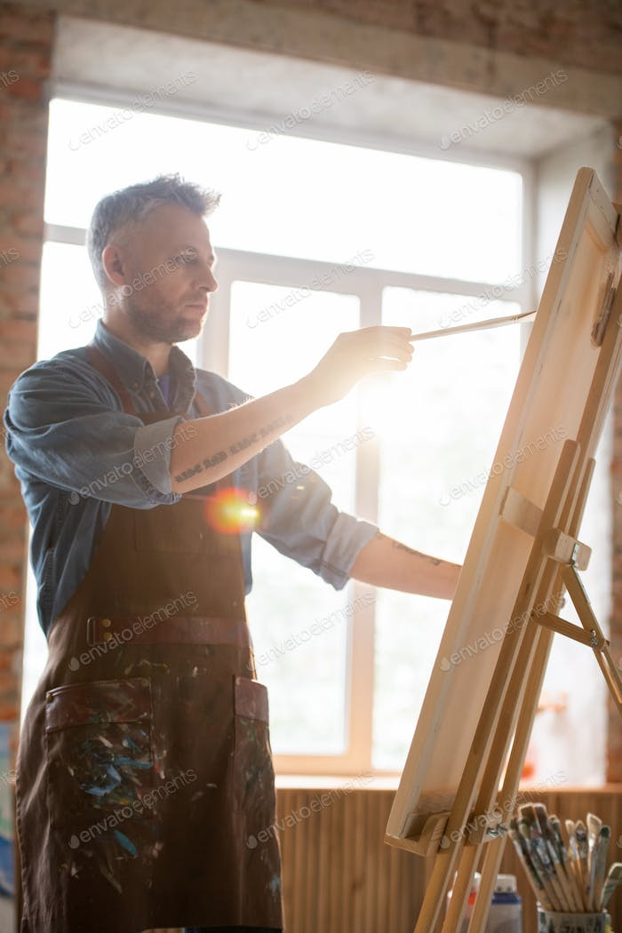Serious male painter holding paintbrush during work in front of easel