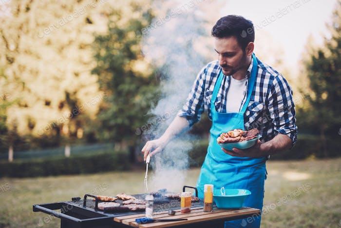 Handsome male preparing barbecue