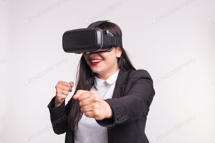 Happy excited young woman using a virtual reality headset on white background