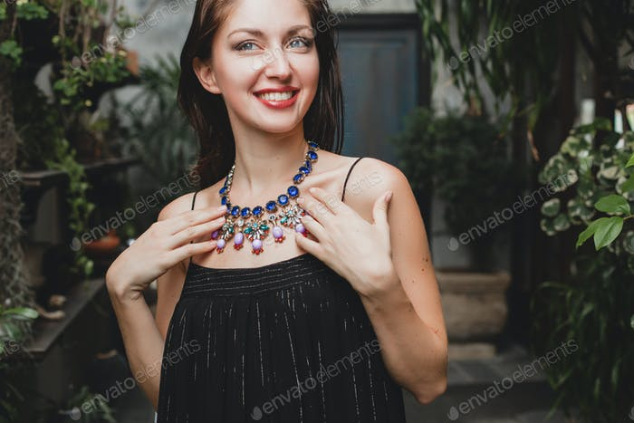 portrait of young attractive woman in elegant black dress wearing luxury rich necklace jewelry
