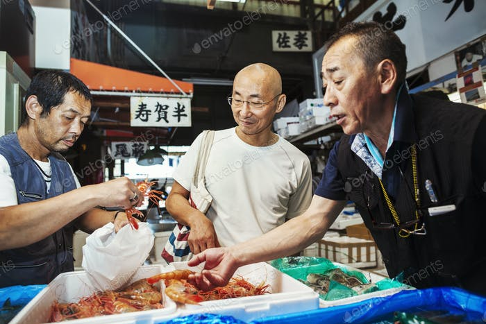 A traditional fresh fish market in Tokyo. Two people selecting shellfish for a customer to buy,
