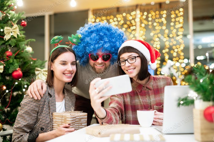 Group of happy colleagues in xmas attire making selfie by workplace in office