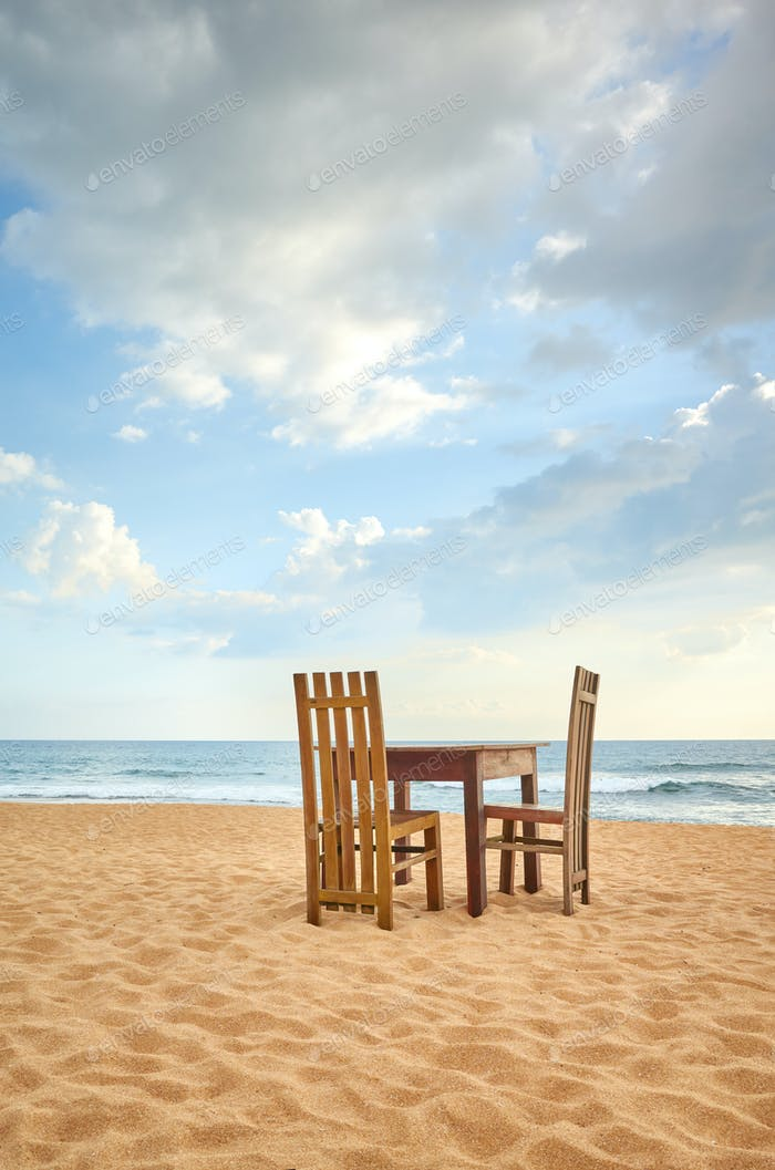 Wooden table and two chairs on a beach.