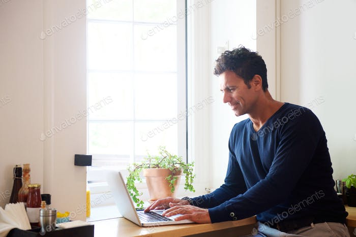 Man working with laptop at indoor cafe