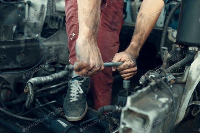 Repairman tries to unscrew part on car junkyard