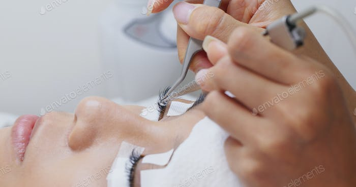 Beautician and young woman in a beauty salon with eye lash extension