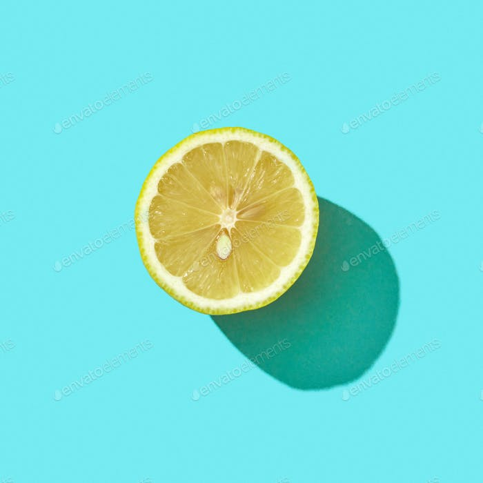 Half a juicy lemon on a blue background with shadow and copy space. Ingredient for drink. Top view
