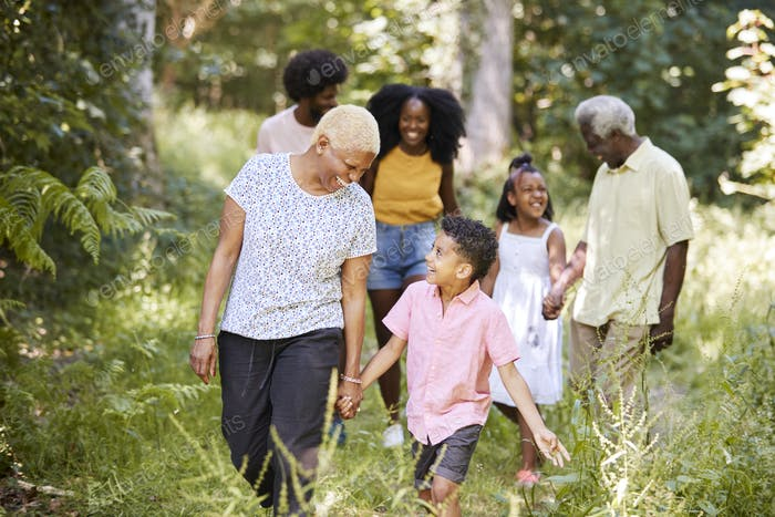 Senior black woman walking with grandson and family in woods