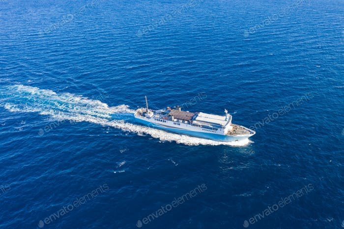 Aerial drone view of a passenger ship, blue sea background.