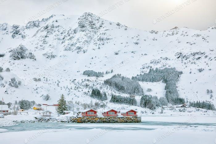 Erstaunliche Winterlandschaft mit traditionellen norwegischen roten Holzhäusern am Ufer