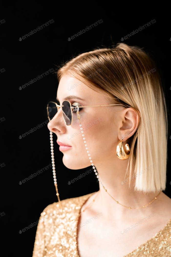 Junge blonde glamouröse Frau in Sonnenbrille, glitzerndes Kleid und goldene Ohrringe