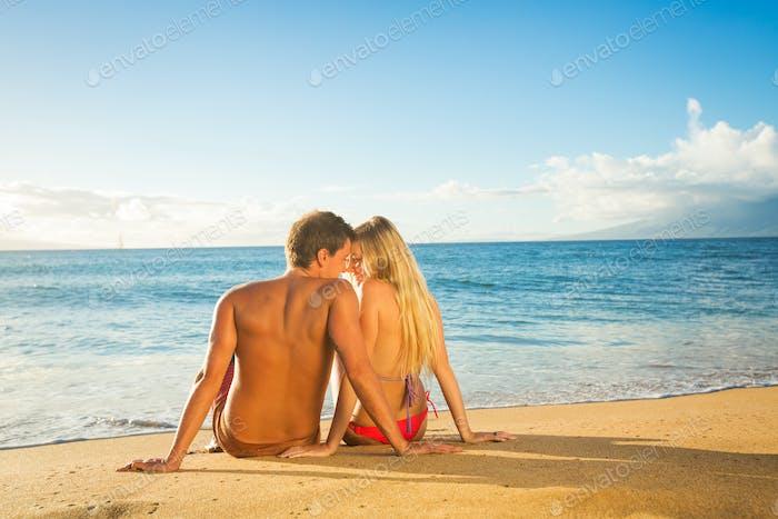 couple sitting on a sandy tropical beach