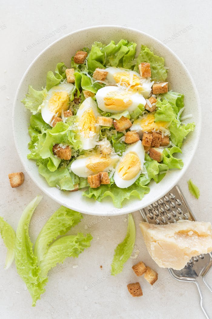 Caesar salad with eggs, lettuce and parmesan cheese on plate. Top view