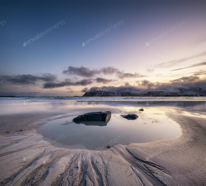 Beach on the Lofoten islands, Norway. Mountains, beach and clouds during sunset.