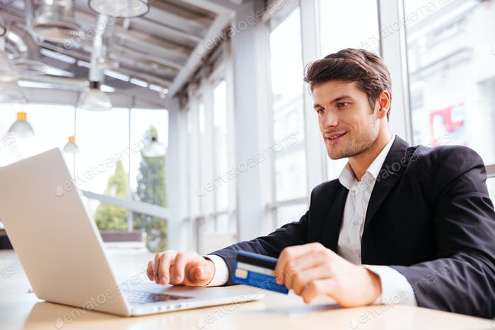 Businessman using laptop and credit card at the table