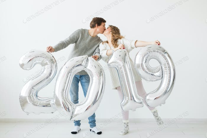New 2019 Year is coming concept - Happy young man and woman are holding silver colored numbers on