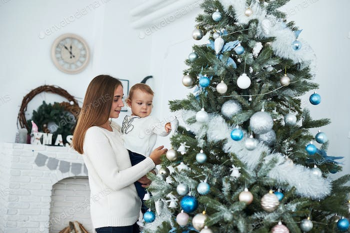 happy family mother and baby decorate Christmas tree