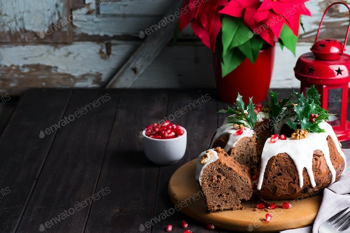 Christmas sliced chocolate cake with white icing, holly branches and pomegranate kernels on a wooden