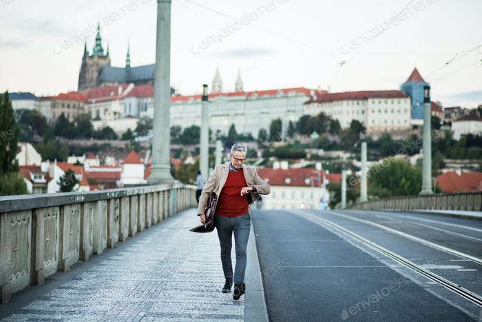 Mature businessman with bag walking on a bridge in Prague city.