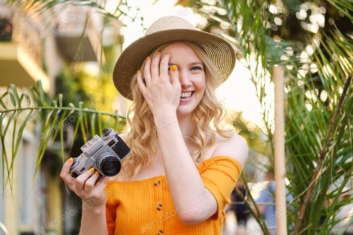 Beautiful romantic blond girl in hat happily holding retro camera in hand on city street