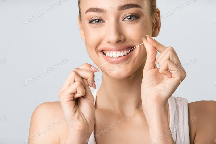 Girl Flossing And Cleaning White Teeth Posing In Studio, Cropped