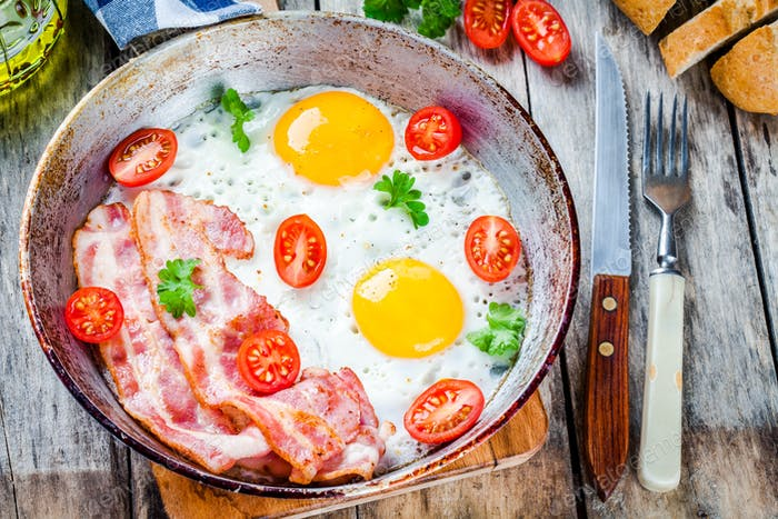 Breakfast with fried eggs, bacon, tomatoes and parsley