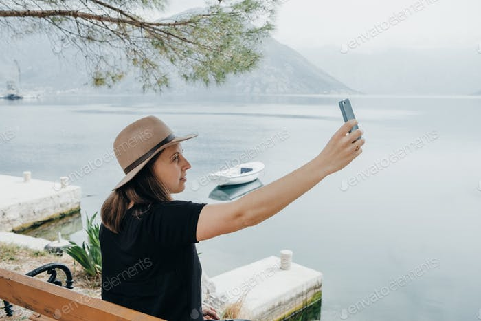Travel woman in a hat making selfie at view of the bay in Montenegro.