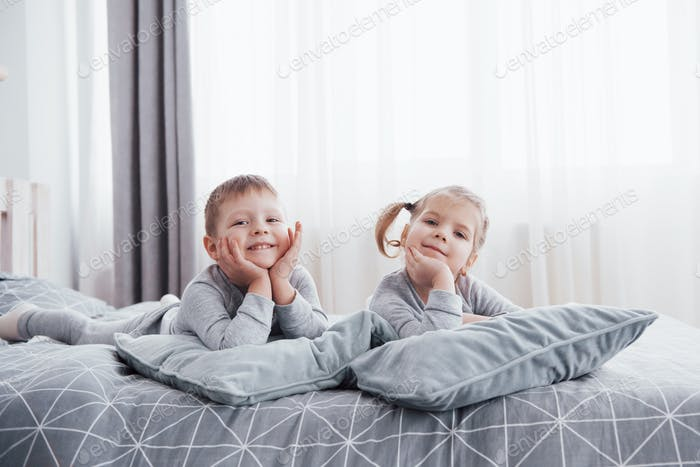 Happy kids playing in white bedroom. Little boy and girl, brother and sister play