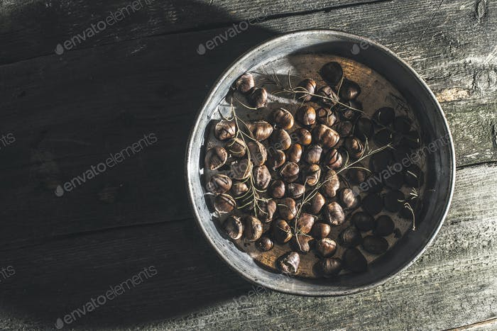 Roasted chestnuts. Vintage baking tray. Natural sun rays from wi