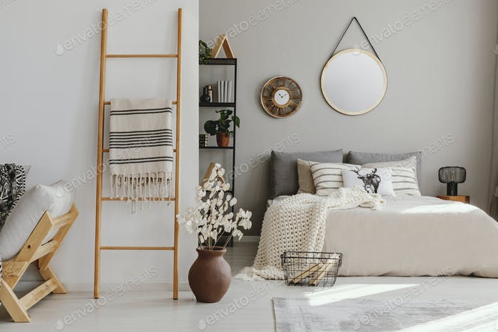 Scandi open space bedroom interior with double bed with knit bla