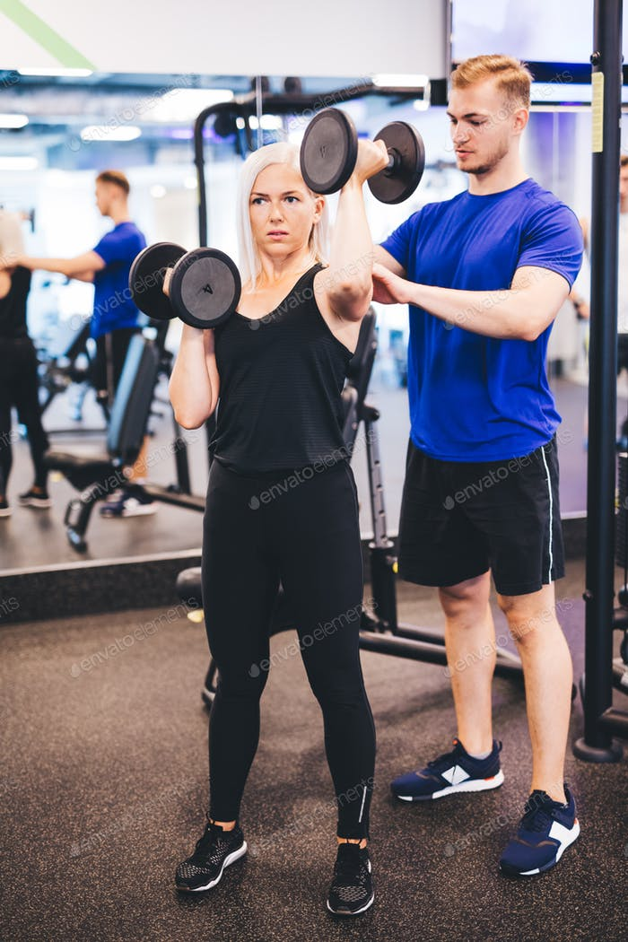 Exercising woman assisted by personal trainer.