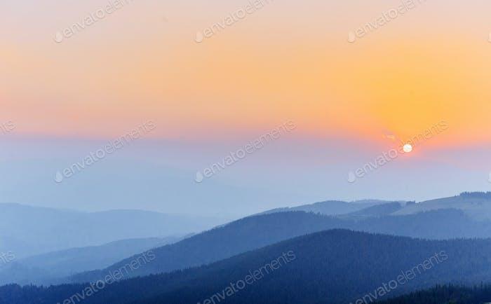 Thick fog and sunrise in the mountains. Carpathians. Ukraine. Eu