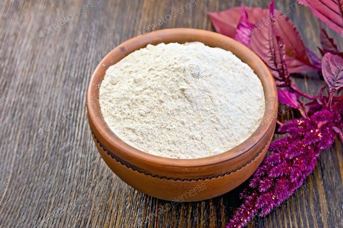 Flour amaranth in clay bowl on board