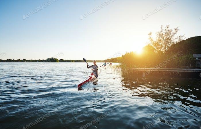 Frau Kajakfahren in den Sonnenuntergang