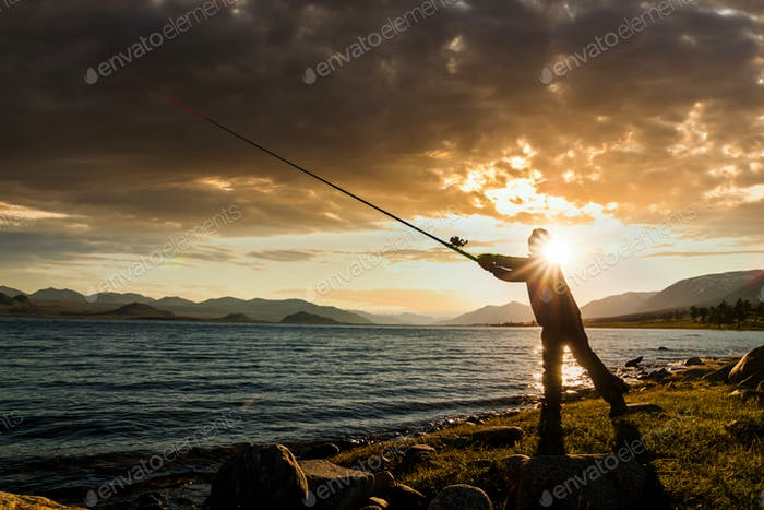 Silhouette of a fisherman at sunset on a lake