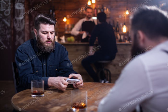 Two bearded hipsters playing a card game in a pub