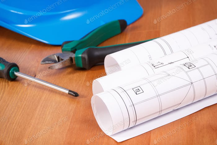 Rolls of electrical drawings, protective helmet and work tools for use in engineer jobs