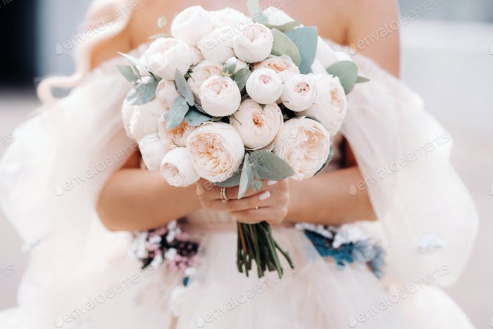 A bride in a wedding dress holds a bouquet of roses in her hands in front of her .close up