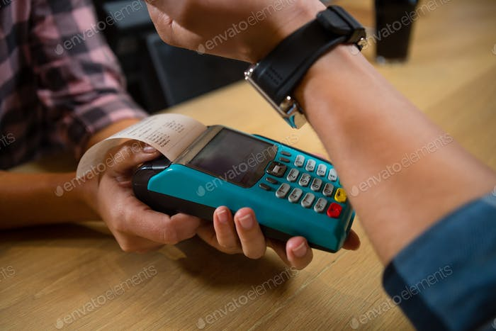 Cropped hand of customer making payment at bar