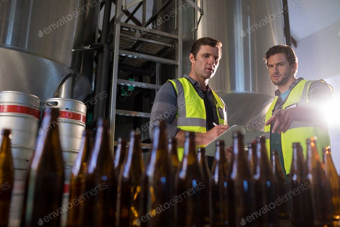 Coworkers discussing while pointing towards beer bottles