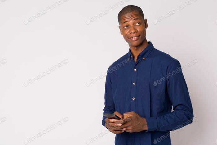 Portrait of young happy bald African businessman thinking while using phone