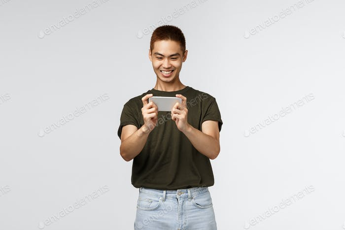 Technology, online lifestyle and communication concept. Happy pleased young asian male using mobile