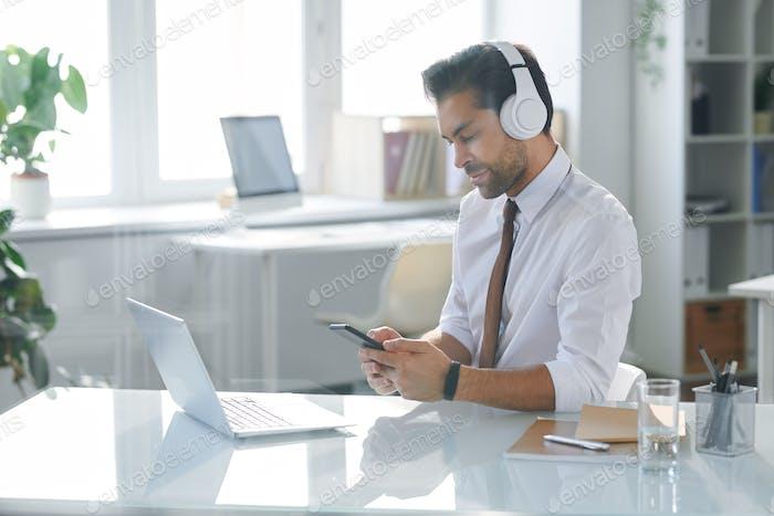 Elegant office worker in headphones looking through playlist